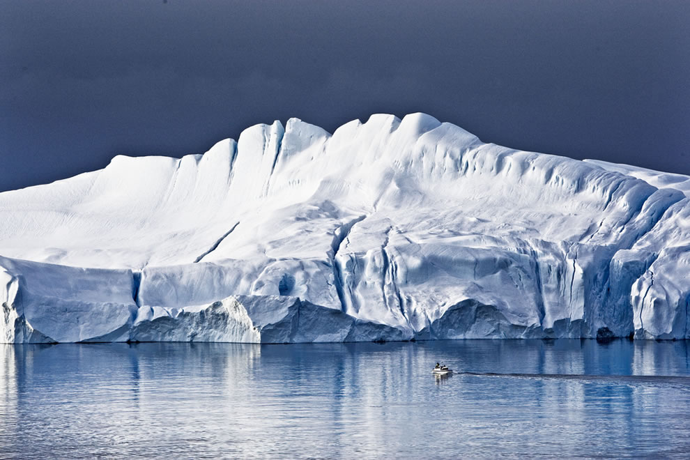 Feeling-tiny-in-Greenland-small-boat-next-to-massively-and-magestic-iceberg