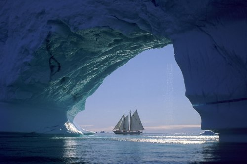 Sailboat-seen-through-huge-iceberg-cave