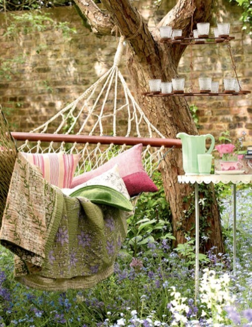 beautiful-outdoor-hammock-with-pillows-and-floral-blanket-and-nice-hanging-candle-with-table-and-tepaot-and-glasses-and-flowers-in-the-garden