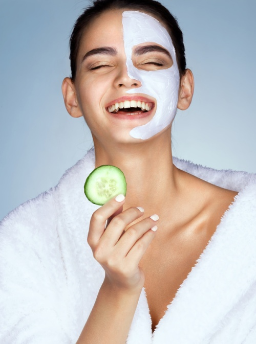 Laughing woman with the slice of cucumber in hand. Photo of funny girl with moisturizing facial mask. Beauty & Skin care concept