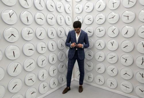 "Visitor looks at mobile phone as he visits the ""Proper Time"" installation by Lee Wan, at the Korean Pavilion, during the 57th Biennale in Venice"